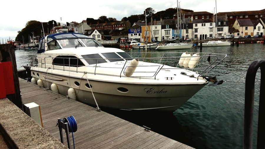 A Seascape Photography at Weymouth Harbour United Kingdom of a Beautiful Boat Moored up. Featuring Nautical Vessel Harbor Sea Transportation Mode Of Transport Water Yacht Luxury Beach Day Outdoors People Sky Sailing Ship Yachting Waterfront Boats⛵️ Houses Holiday