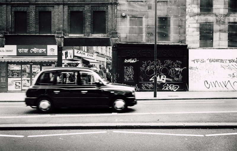 35mm London VSCO Architecture Black And White Blurred Motion Building Exterior Built Structure Car City Day Land Vehicle Leica Mode Of Transport Motion One Person Outdoors People Public Transportation Real People Road Street Text Transportation