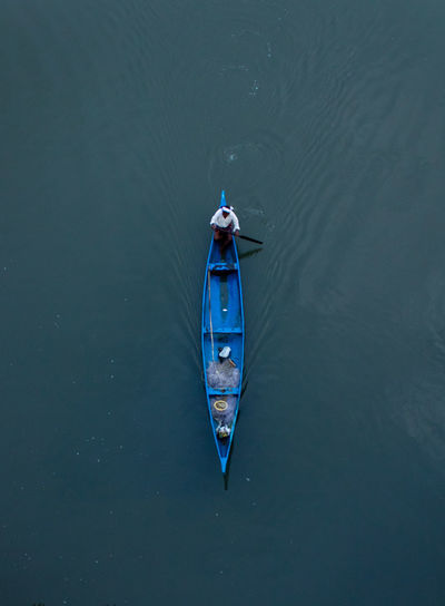 High angle view of man sitting in fishing boat on sea