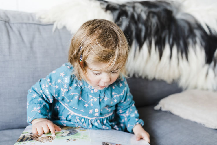 Cute Girl Reading Book On Sofa