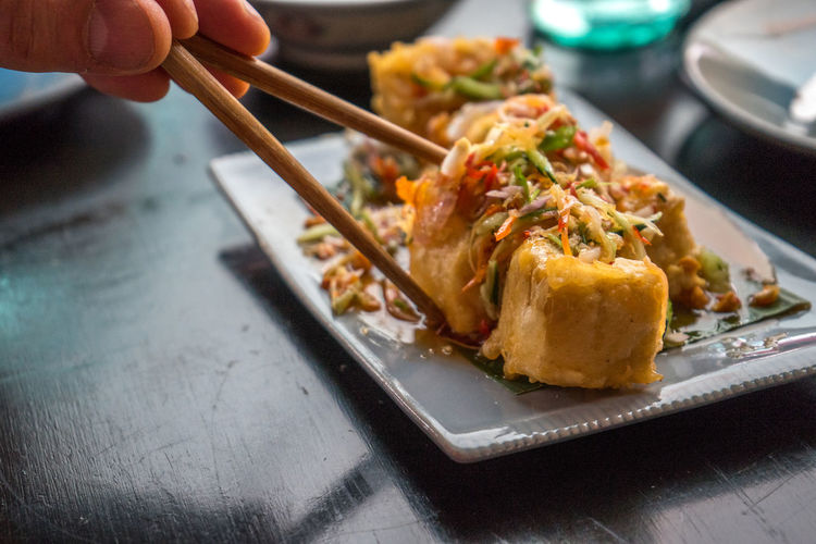 Cropped Image Of Hand Holding Tofu With Chopsticks
