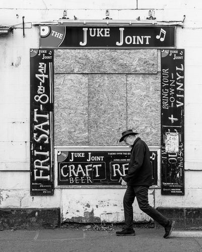 The Juke Joint Communication Text Western Script Full Length Sign Real People One Person Men Architecture Day Casual Clothing Built Structure Wall - Building Feature Non-western Script Script Building Exterior Walking Capital Letter Lifestyles Outdoors