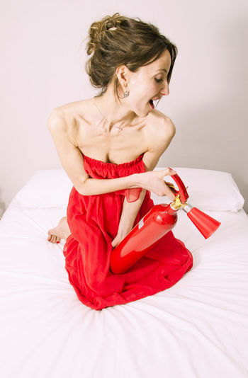 25-35 Old Woman Brunette Cool Domestic Room Extinguisher Extinguishing Extinguishing Fires Fire Fun Times Girl In Bed Having Fun Pink And Hot Pink Color Pink Color Playing Games Portrait Red Red Dress Red Extinguisher Skinny Girl Skinnygirls Smiling Smiling Face