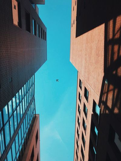 Directly below shot airplane flying over buildings in city