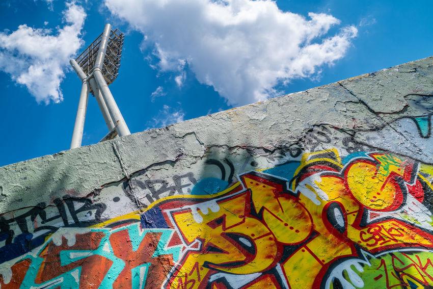 Mauerpark am Friedrich-Ludwig-Jahn Sportpark Berlin Berlin Art And Craft Blue Built Structure Cloud - Sky Communication Creativity Graffiti Multi Colored Nature No People Outdoors Sky Text Wall Wall - Building Feature
