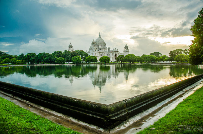 Panoramic view of temple by lake against sky