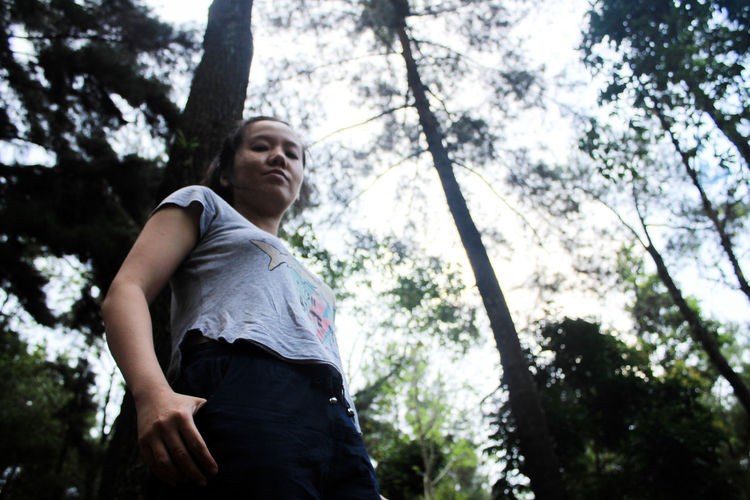 Low angle portrait of woman standing against tree in forest
