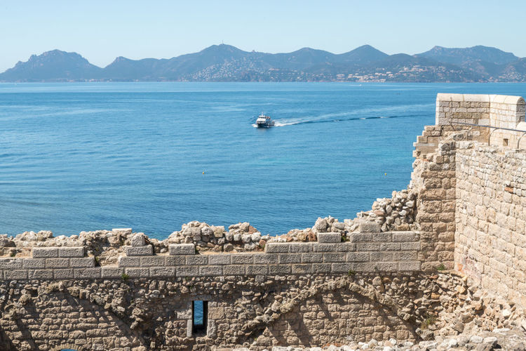 fortified island and monastery of Saint Honorat in Cannes (France) île et monastère fortifié de Saint Honorat à Cannes Island Island Of Lerins Iles De Lerins île Saint Honorat Cannes Monastery Monastère Water Sea Architecture Sky Mountain Day Built Structure Building Exterior No People Nature Nautical Vessel Scenics - Nature Wall History Beauty In Nature Fort Travel The Past Travel Destinations Outdoors Stone Wall