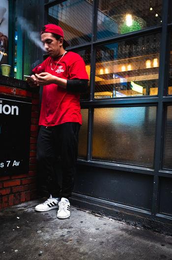 Full length portrait of man standing on mobile phone