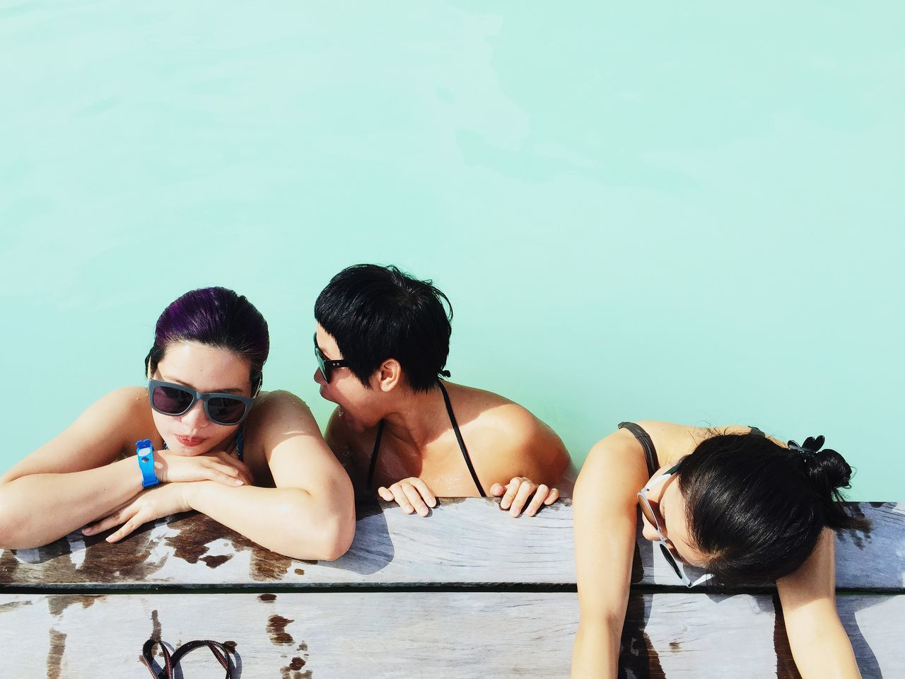 High Angle View Of Friends In Swimming Pool On Sunny Day