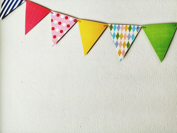 Close-up of multi colored paper flags against wall