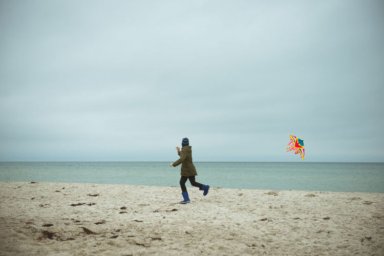 Rear view of boy holding kite running on beach against sky