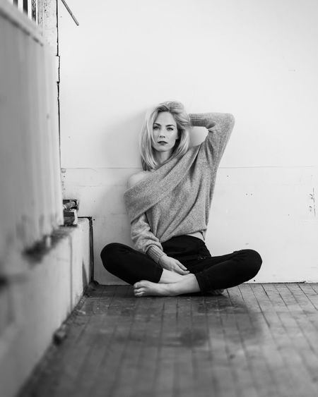 Portrait of woman sitting on floor at home