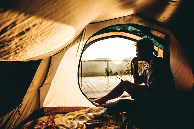 Side view of man sitting in tent during sunset