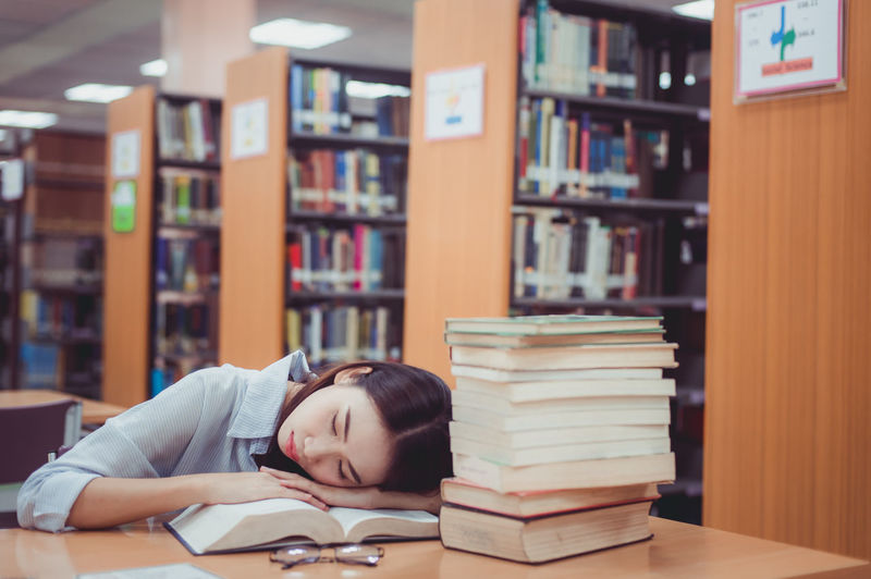 Young woman sleeping at table in library