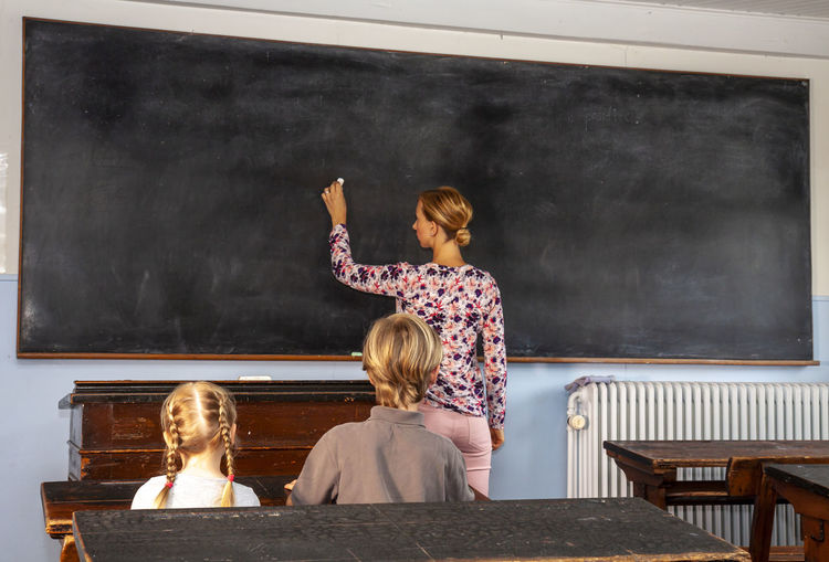 Rear View Of Teacher Teaching Students In Classroom