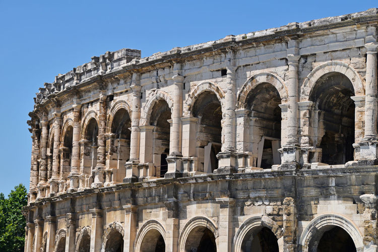 The Arena of Nimes is a Roman amphitheatre Archaeology Ancient History Ruined Outdoors Ancient Civilization Building Exterior Old Ruin Day Tourism Low Angle View Arts Culture And Entertainment Built Structure Travel Ancient Amphitheater Travel Destinations Architecture The Past History Arch Arena Clear Sky Copy Space Famous Place Landmark