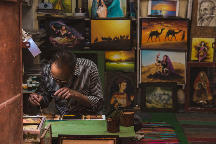 An artist at work ... Jaisalmer Rajasthan Streetphotography Travel Colorful Working Occupation City Men Multi Colored Workshop Craftsperson Skill  Business Finance And Industry Art Studio Craft Fine Art Painting Acrylic Painting Paintings Art Artist's Canvas Painter - Artist Oil Paint Modern Art Art And Craft Equipment Brush Stroke Paintbrush Palette Oil Painting Carving - Craft Product The Photojournalist - 2019 EyeEm Awards The Traveler - 2019 EyeEm Awards The Street Photographer - 2019 EyeEm Awards