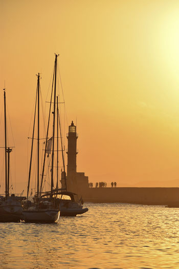 Sunset colors at the old town of Chania Lighthouse Orange Sky Silhouette Sunset_collection Beauty In Nature Clear Sky Mast Mode Of Transportation Nature Nautical Vessel No People Orange Color Outdoors Pole Sailboat Sailing Scenics - Nature Sea Sky Summer Sunset Transportation Travel Water Waterfront