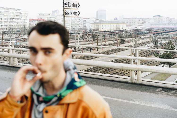 Train Station Smoke Smoking Architecture Looking At Camera Focus On Background City Men Headshot Technology Holding Human Hand Close-up Cityscape Urban Skyline Urban Scene
