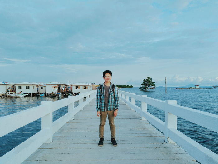Full Length Of Young Man Standing On Footbridge Over Sea Against Sky