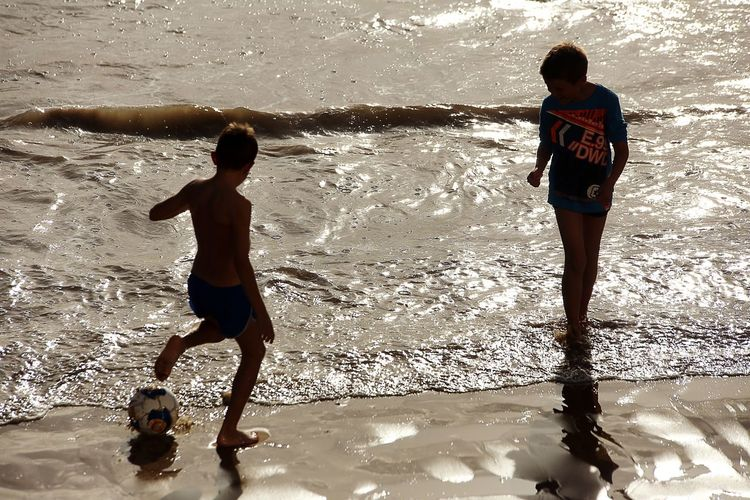 Beach game Children Boys Football Sea Nature Sport Holidays SunAgainst The Light Full Frame Sand Wave La Baule, France Outdoors Water Games