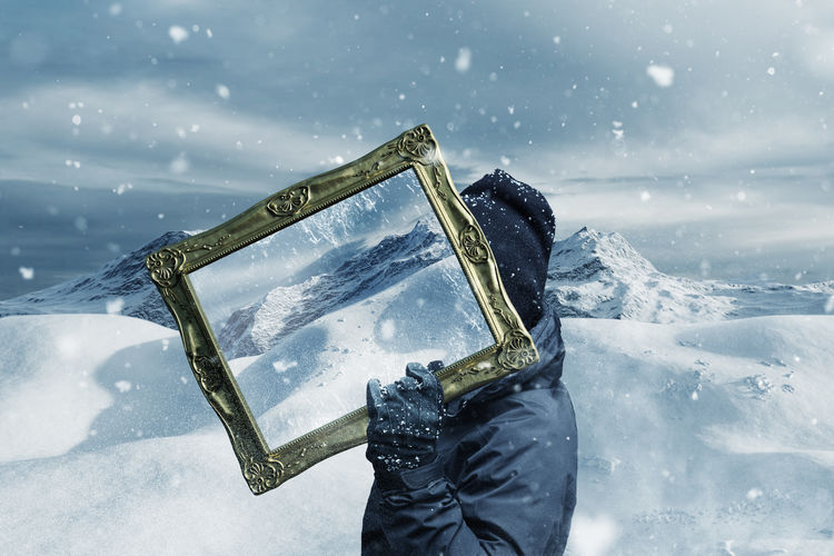 Side view of person holding mirror during snowfall