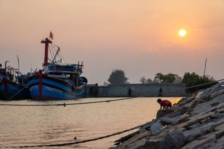 Boys with beauty of nature. Moored Boats Twilight Vietnam Bay Beauty In Nature Blurred Background Boat Boy Estuary Fishing Boat Fishing Industry Kid Lifestyles Moored Nature Nautical Vessel One Person Orange Color Outdoors Port Rock - Object Scenics - Nature Selective Focus Sky Sunset