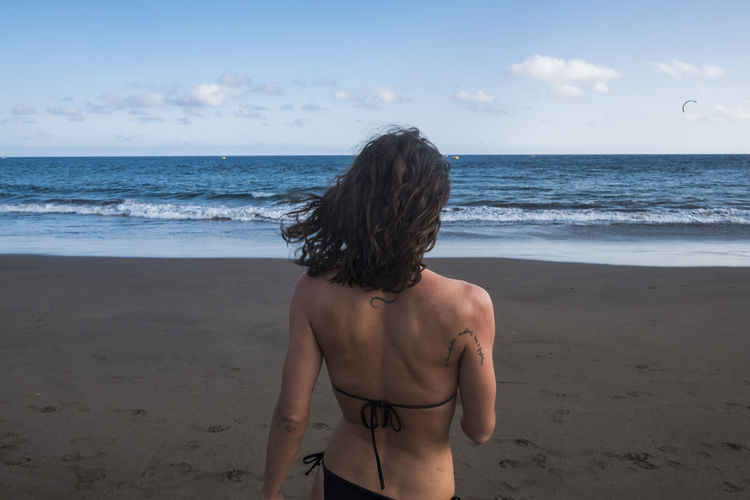 Rear view of woman wearing bikini standing at beach against sky during sunset