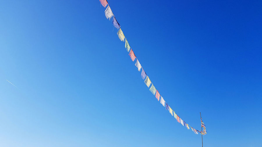 Low angle view of prayer flags hanging against clear blue sky