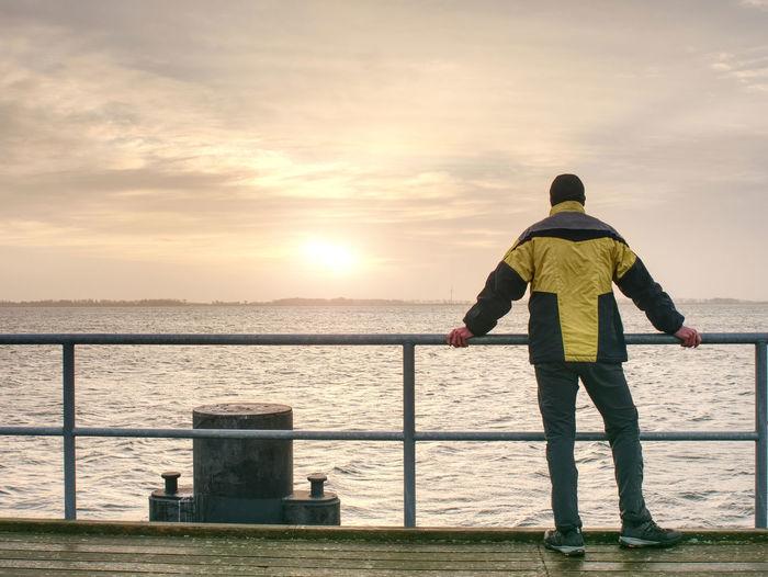 Man tourist in autumn mist on wooden pier above sea. depression dark atmosphere.