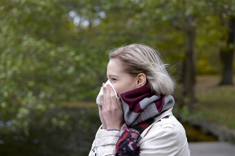 Young woman blowing nose while standing against trees