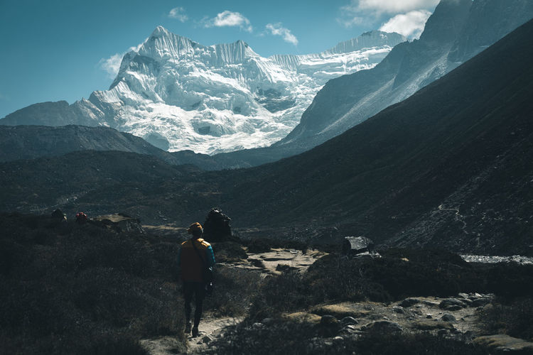 Rear View Of Man Walking Against Snowcapped Mountains