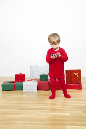 Full length of boy playing with toy against white background