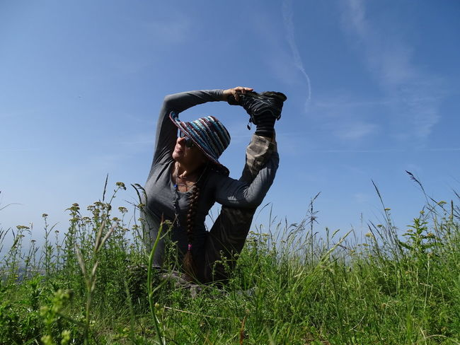 Relaxing Relax Yoga Yoga In Nature Green Landscape Yoga Pose Headwear Sitting Full Length Sky Grass Posture Fitness Zen-like Countryside Exercise Mat Meditating Yoga Studio Yoga Class Lotus Position