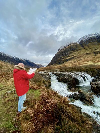 Rear view of person by river coe against sky