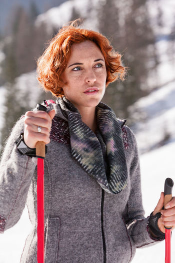 Woman holding ski poles while standing outdoors
