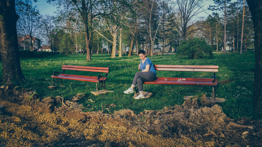 Full length of woman sitting on bench against trees in park