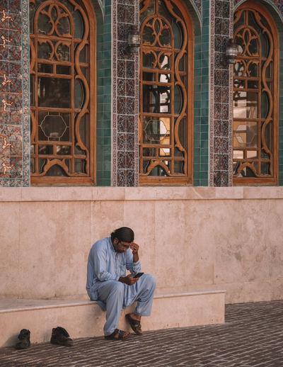 Full length of men sitting on wall against building