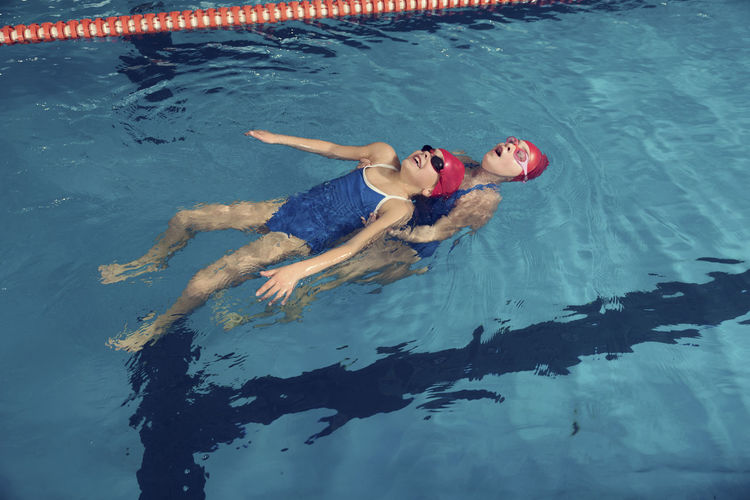 High angle view of girl with coach swimming in pool