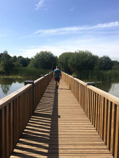 Rear view of man on footbridge over lake against sky
