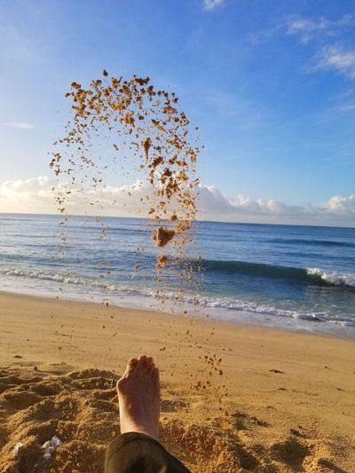 Low section of person kicking sand at beach against sky