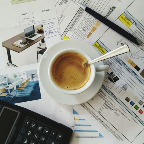 High Angle View Of Coffee With Calculator And Documents On Table