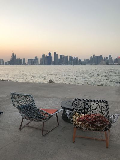 Deck chairs and tables by sea against sky during sunset