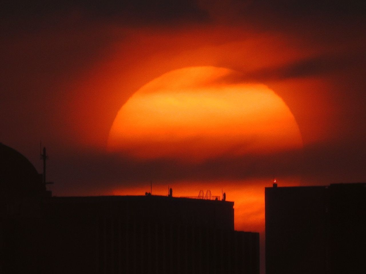 sky, sunset, orange color, architecture, silhouette, building exterior, built structure, sun, beauty in nature, nature, no people, cloud - sky, building, scenics - nature, dramatic sky, city, outdoors, idyllic, environment, technology, romantic sky
