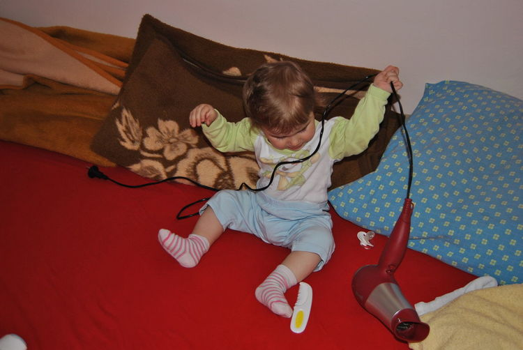 Boy playing with hair dryer on bed at home