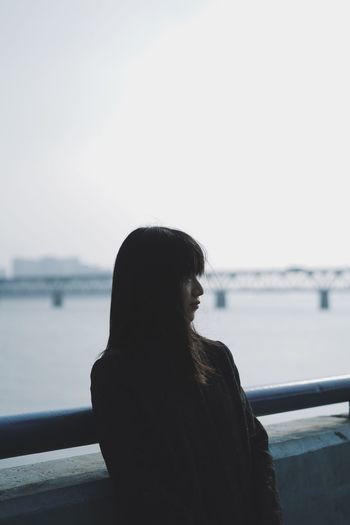 Young woman looking away while standing against river
