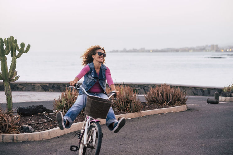 Cheerful woman riding bicycle on road against sea