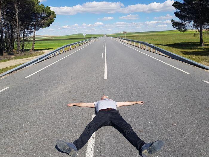 Full length of man lying on road