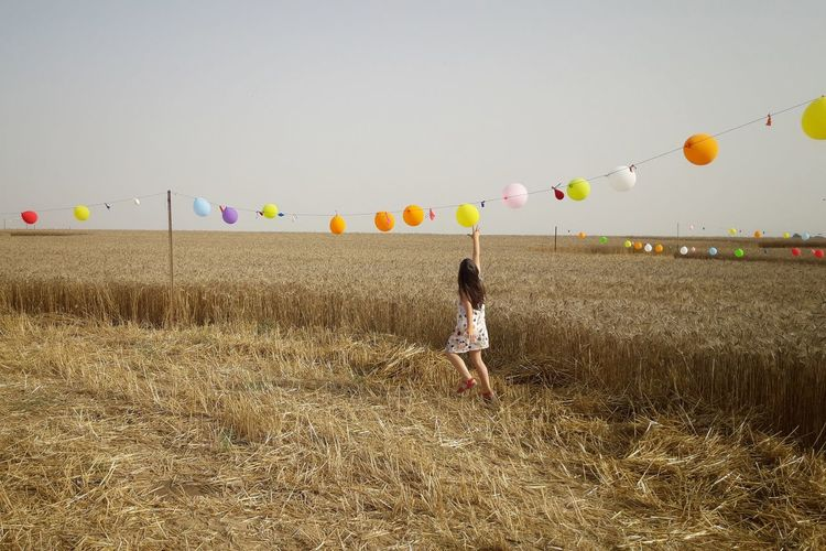 Rear view of girl exploding balloons hanging on string at farm against clear sky